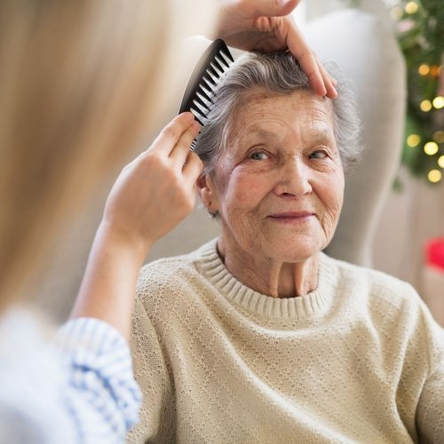a-health-visitor-combing-hair-of-senior-woman-at-YZF2RQ8-1600-80